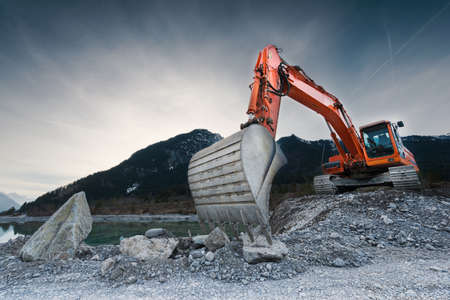 construction: heavy organge excavator with shovel standing on hill with rocks