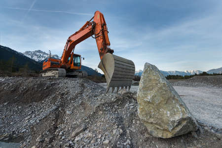 huge shovel excavator standing on gravel hill with stone rock
