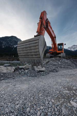 perspective of huge shovel with excavator digging in stone gravel Standard-Bild