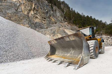 front loader: enorme pala de cargadora de ruedas en cantera de piedra con la colina de grava Foto de archivo