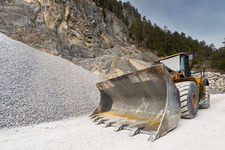 wheel loader: huge shovel of wheel loader at stone quarry with gravel hill