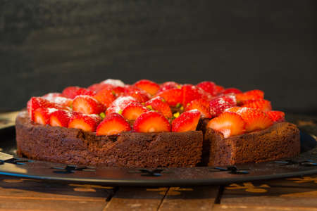 wit: fresh chocolate cake wit red strawberries on wooden table