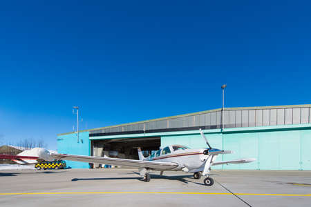 private jet: small aeroplane standing before aircraft hangar at blue sky