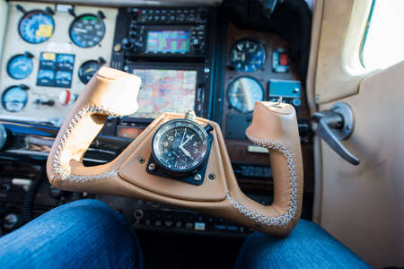 altimeter: brown leather steering wheel of small propeller aircraft