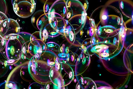 burbuja: coloridas burbujas de jabón volando alrededor sobre fondo negro Foto de archivo