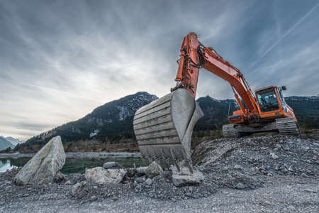 big orange digger on gravel heap with big shovel 스톡 콘텐츠