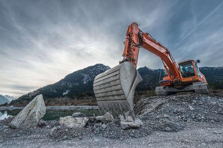 aparatos electricos: gran excavadora de naranja en el montón de grava con la pala grande Foto de archivo