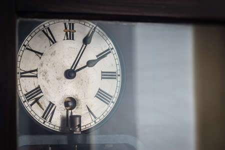 metall and glass: old retro clock with roman numerals behind glass
