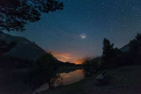starry night with blood moon at alpine lake and wooden bench