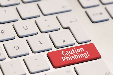 phishing: computer keyboard with the words caution phishing on red key
