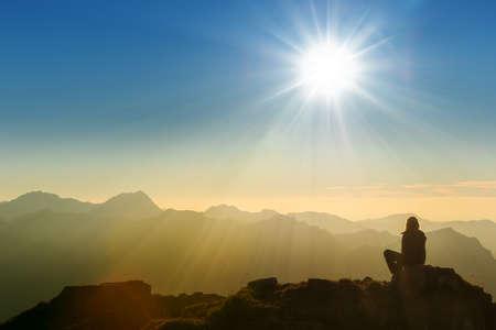 eenzaam triest persoon zit op bergtop in de vroege ochtend