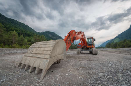 gravel: heavy red digger with huge shovel in gravel