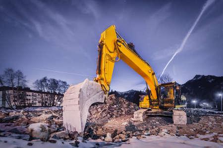 huge orange shovel digger on demolition site at night