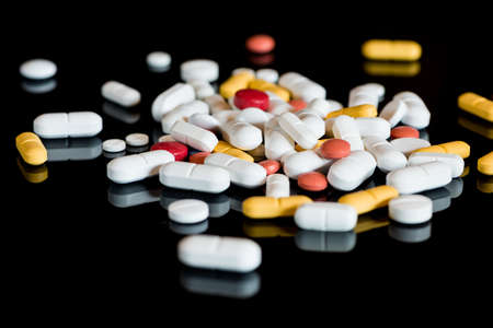 colores: a lot of colored drug pills on black background Stock Photo