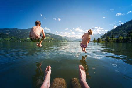 meisje en jongen springen in lake water op zomervakantie