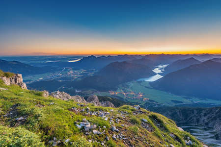 valley view: view from top of mountain to valley with lake plansee at sunrise