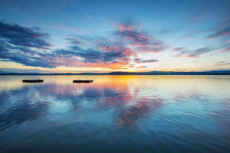 sunset lake: colorful sunset clouds at blue lake with wooden plateaus in austria Stock Photo
