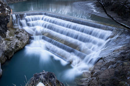 water flowing: water in motion flowing over fall with steps at winter Stock Photo