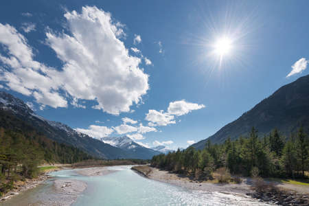 flowing river: sun and clouds over flowing river at austrian mountains