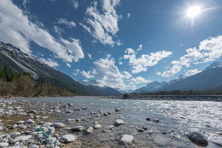 flowing river: stone bank at flowing river lech in tirol lechtal aith blue sky and sun Stock Photo