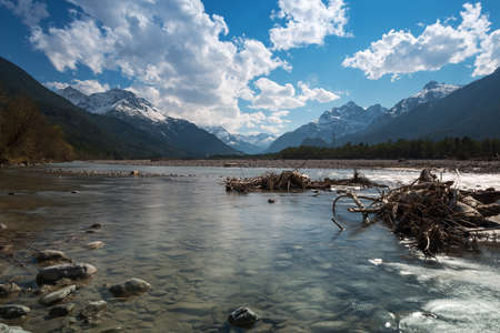 flat water of rural river with stones at blue sky in spring Stock Photo