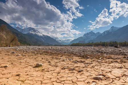 cracked: dry cracked earth ground with stones in mountain land at blue sky