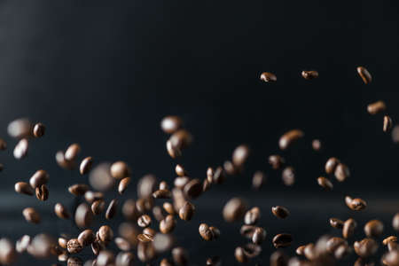 many flying coffee beans on black background