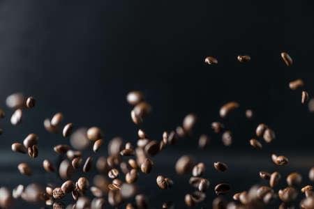 Vele vliegende koffiebonen op zwarte achtergrond