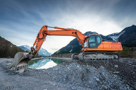 side view of orange shovel digger on gravel at lake and blue sky Stock Photo