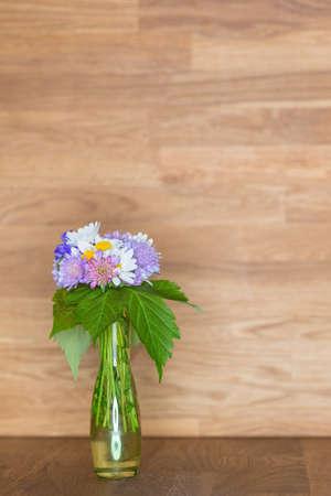 hand picked flowers in vase on wooden background and copy space