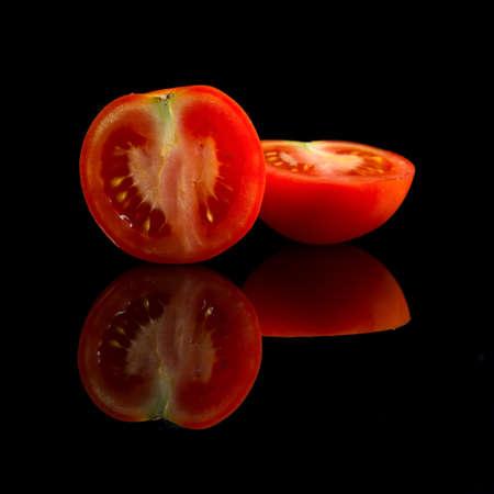 fresh halfed red tomato on black background Stock Photo