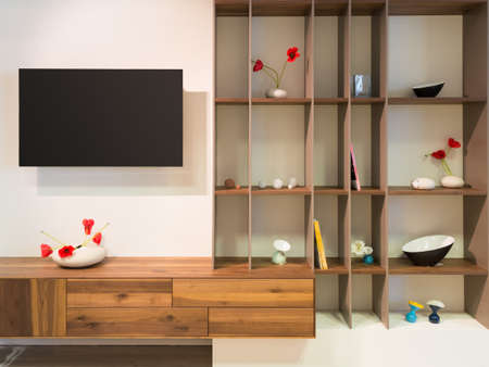 living unit: television on wall an wooden timber shelf units with decoration Stock Photo