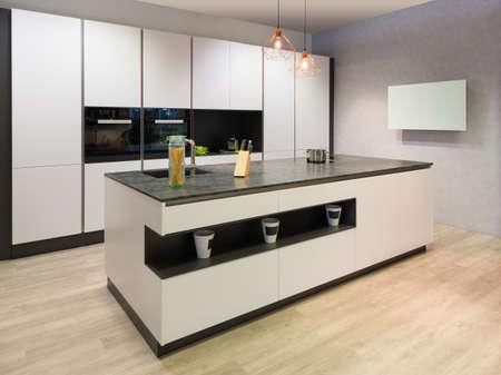 moderne platte witte keuken met kookeiland en tv Stockfoto