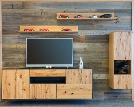 designer living room wall with tv wooden cupboard and shelf Stock Photo