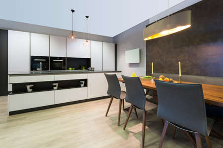modern elegant white flat kitchen with island and dining table Stock Photo