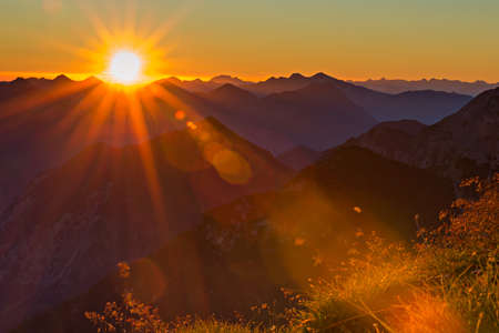 red orange sunset with sunbeams to grass in tyrol mountains