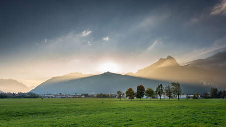 Mountainchain Hahnenkamm in Tyrol with sunbeams from behind the summit