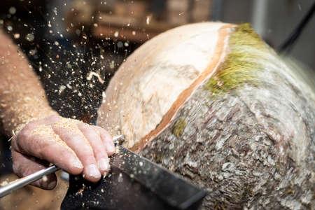 Wood working man cuts rotating piecee of timber on turnery machine