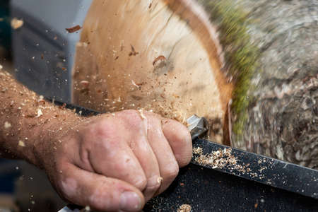 Wood sawdust shavings squirting while creating timber bowl on turnery Stock Photo