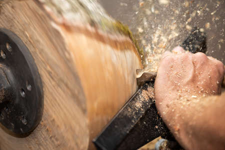 Hand of man cuts piece of timber with flying sawdust and shavings