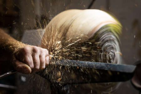 Flying wood shavings while cutting and carving wooden bowl on turnery machine Stock Photo