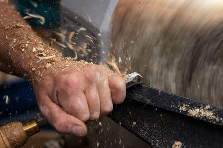 Wood in rotating motion while cutting and carving a timber bowl Stock Photo