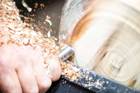 closeup of rotating wood and hand with turnery and flying sawdust shavings