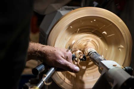 making a hole into a wooden bowl on turnery machine with chisel