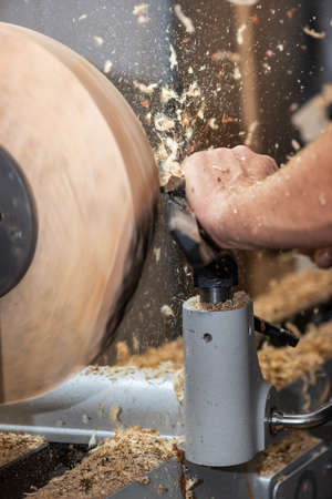 rotating piece of wood and fyling sawdust while making a bowl Stock Photo