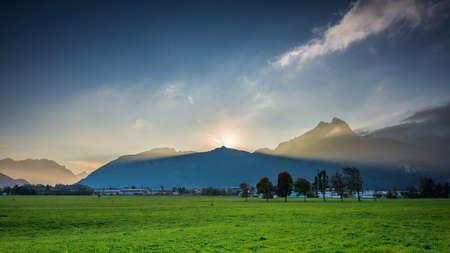 volume light beams of sunset sun behind peak of mountain chain in austria holiday