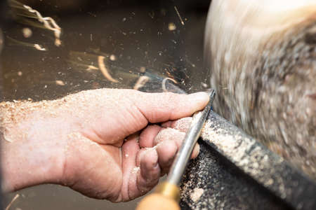 motion of flying sawdust shavings with chisel while turnery of bowl Stock Photo