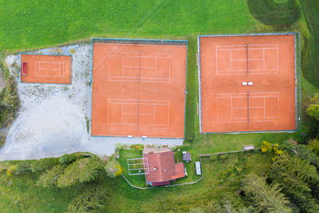birds eye view to four orange clay tennis courts in green meadow landscape