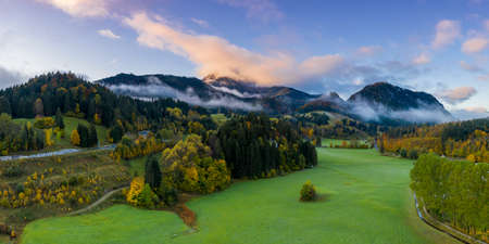 rural landscape with fall autumn trees forest with cloud banks and mountains Stock Photo