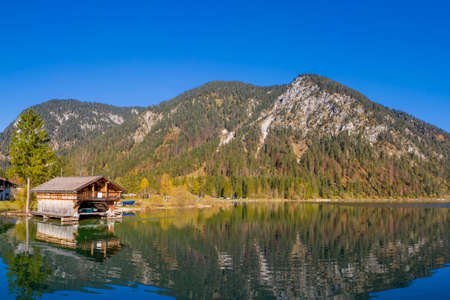 boathouse with reflections in clean blue lake plansee at fall in austria